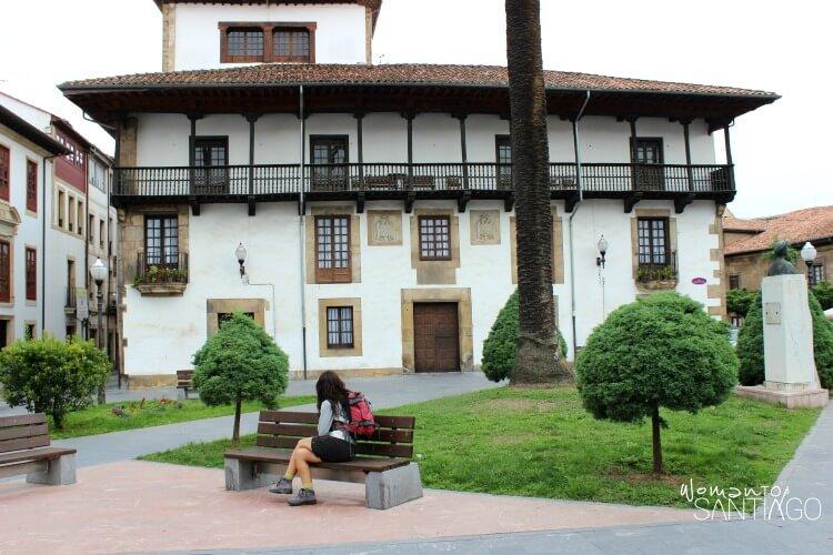 peregrina descansando en un banco con una preciosa casa detrás