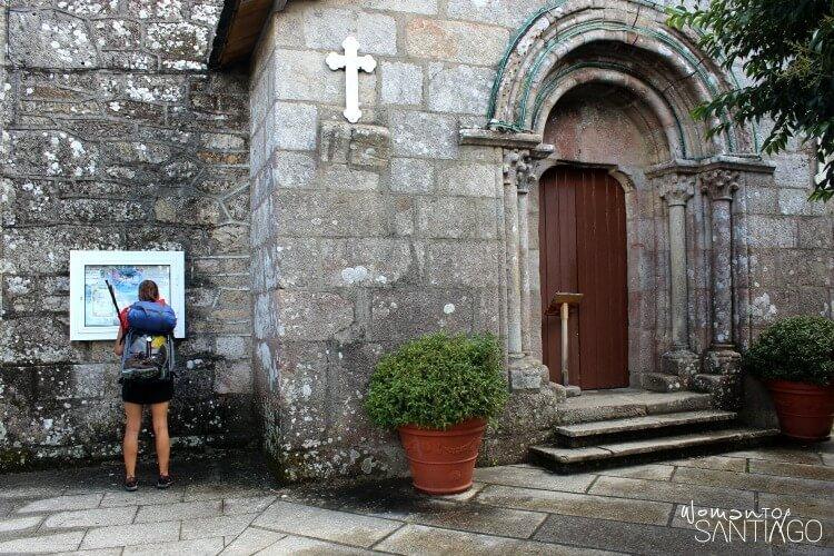 foto de peregrina mirando mapa en la pared de una iglesia