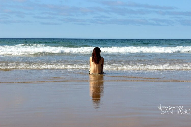 foto de peregrina en la playa tomando el sol en la orilla