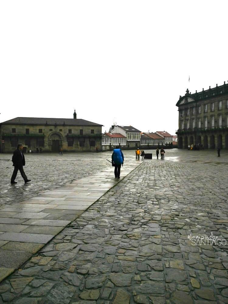 plaza del Obradoiro en Santiago de Compostela con peregrina y con mochila andando