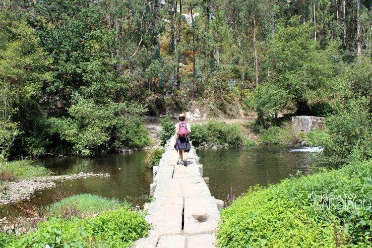 peregrina cruzando un puente de un río
