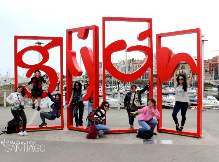 el equipo del camino posando en escultura con el nombre de Gijón
