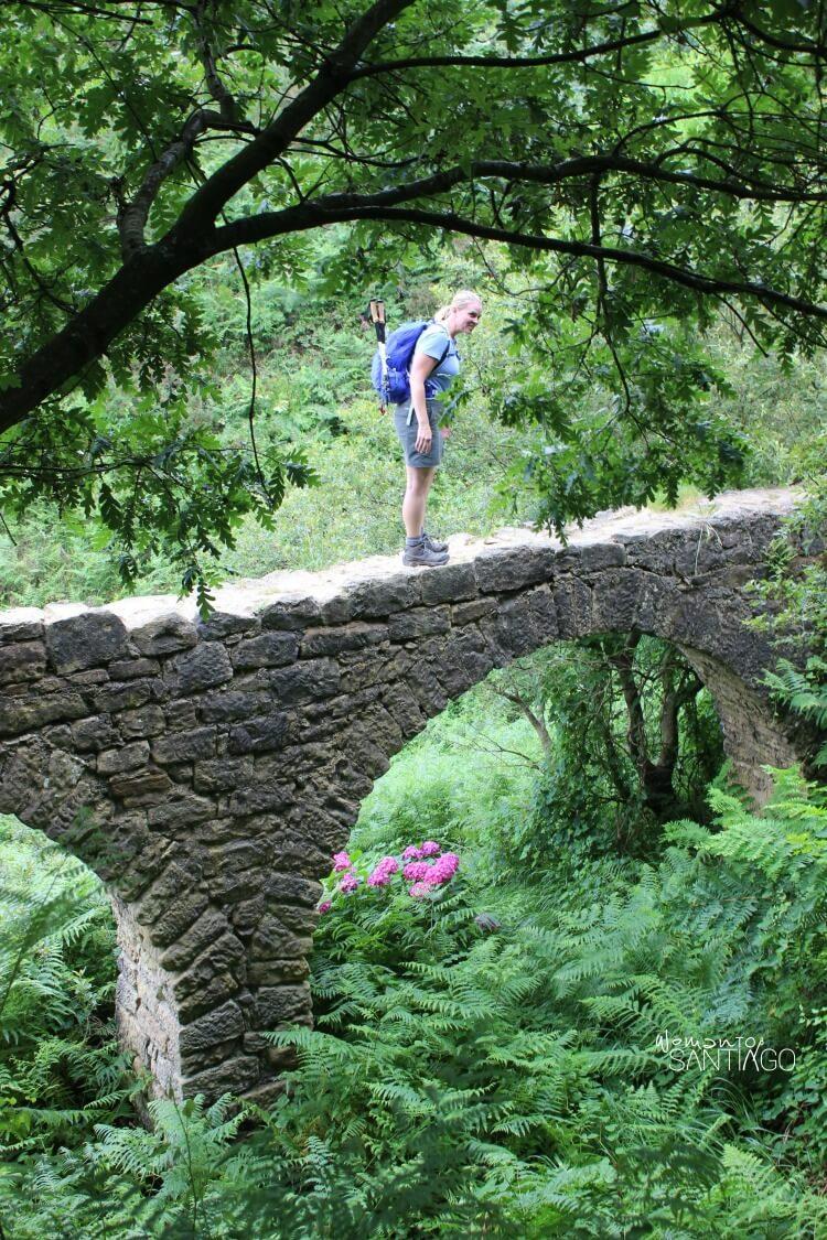 heidi encima de un puente de piedra rodeada de naturaleza