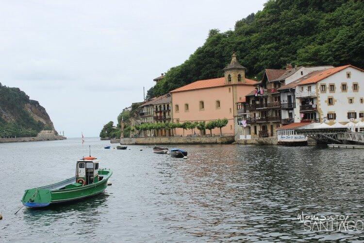 foto de pueblo marinero con barca en medio