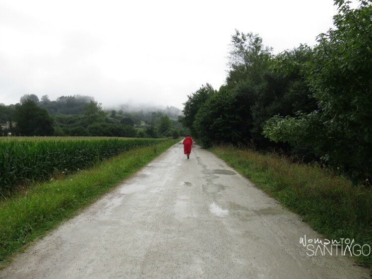 peregrina con abrigo rojo caminando sola