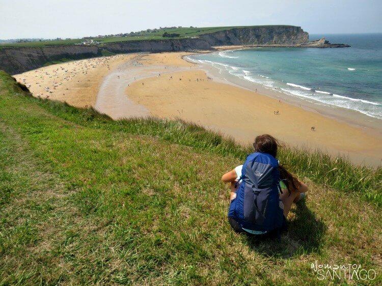 noelia sentada en una pradera verde mirando el mar