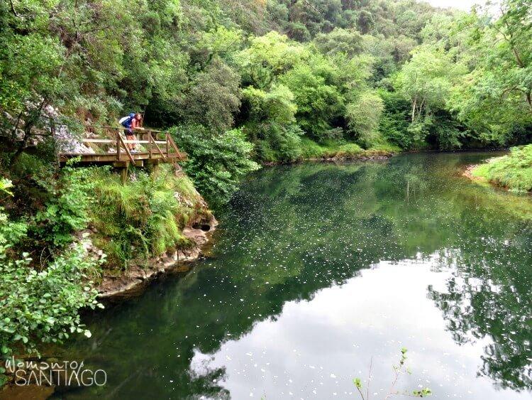 peregrina apoya en un puente con río debajo