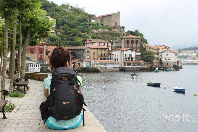 Mujer con mochila de espaldas en pueblo costero del Camino de Santiago