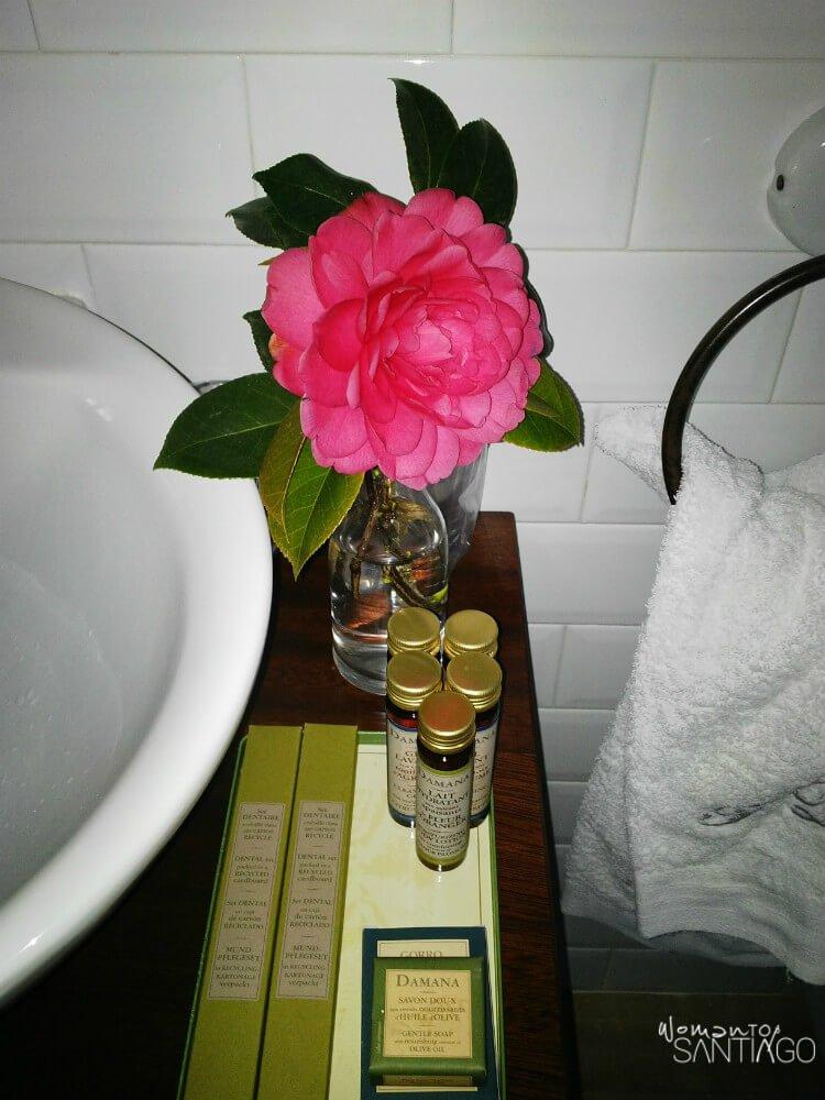 detalle de flor en el baño juntos a amenities