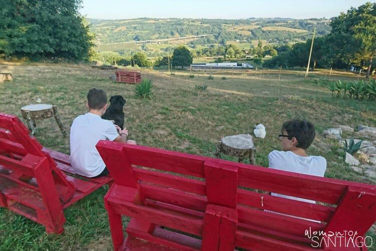 niños contemplando un paisaje con perro en dos bancos rojos