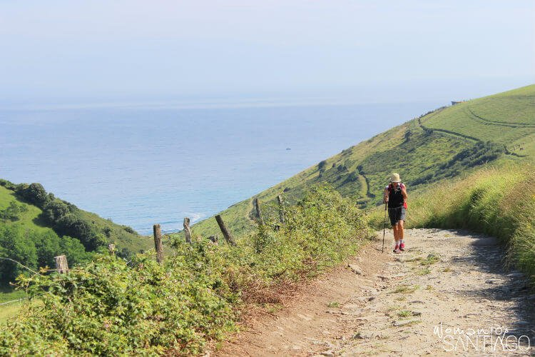 peregrina caminando por una senda con el mar al fondo