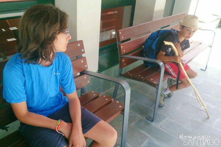 niños en el camino sentados en dos bancos