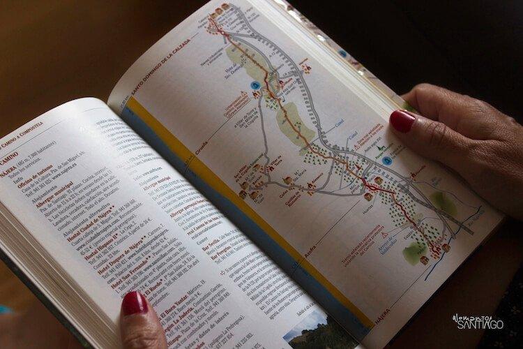 Manos abriendo libro guía sobre el Camino de Santiago