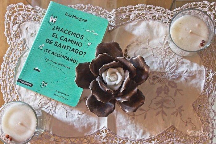 mini guía del Camino de Santiago color verde sobre mesa con dos velas