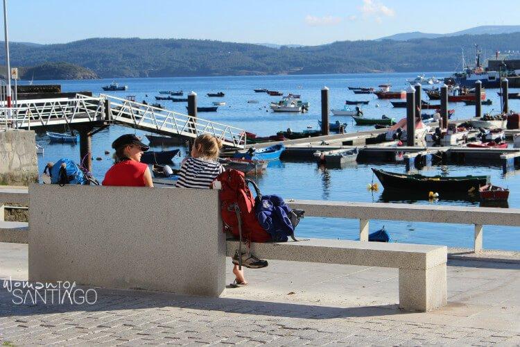 mujeres hablando en un banco frente al puerto