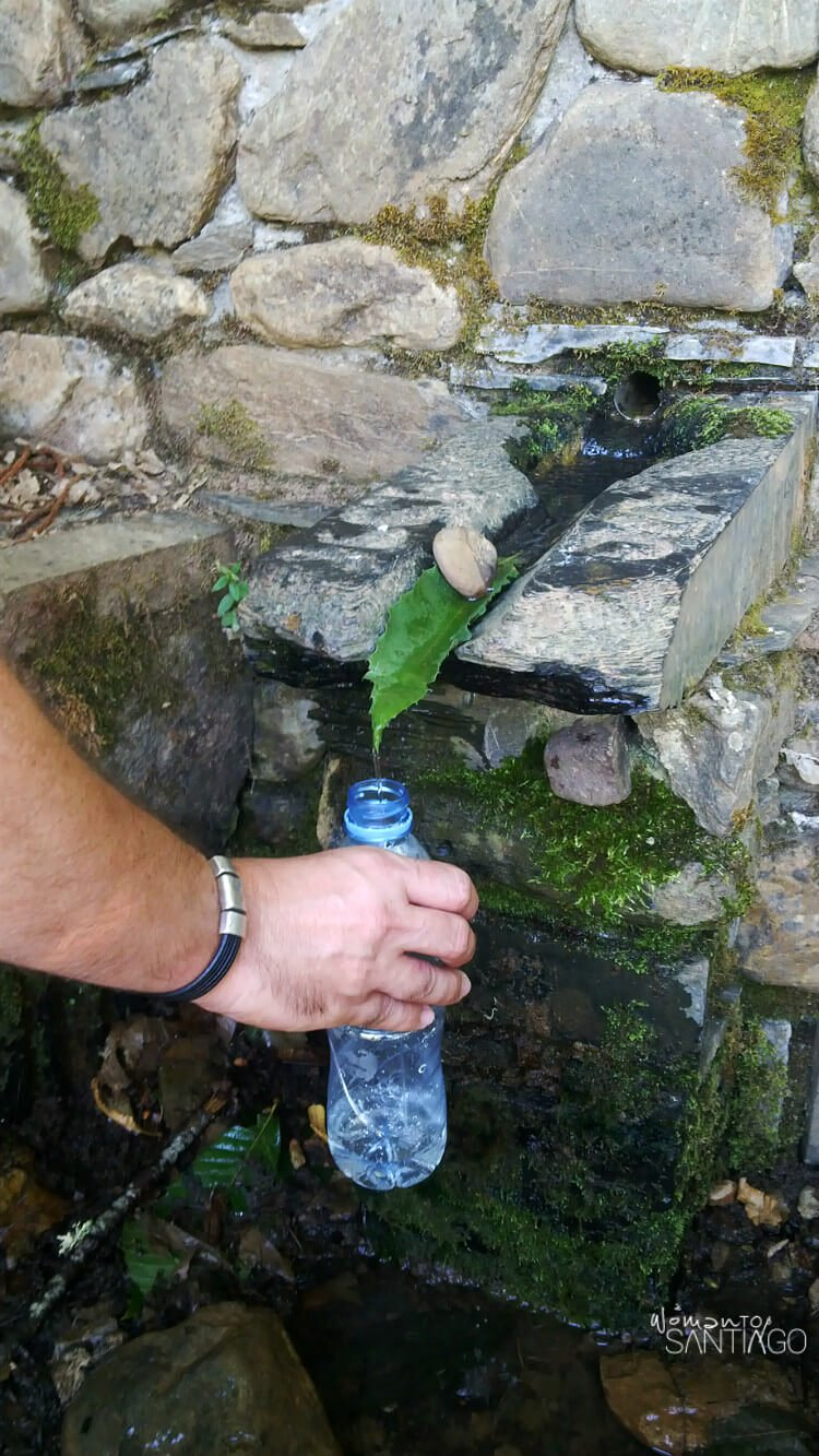 Botella de agua rellena de agua de un manantial