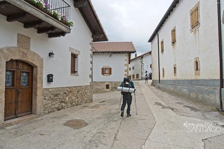 peregrino caminando con mochila por una callejuela