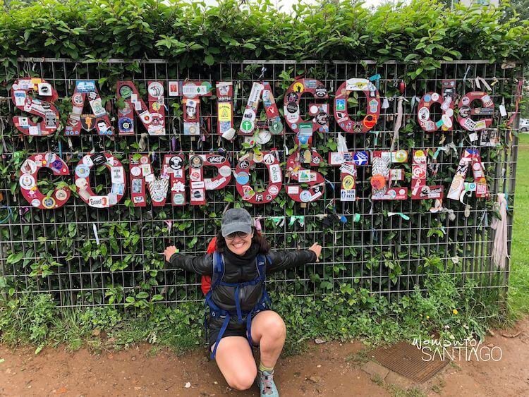 Noelia posando en un letrero del Camino, sonrriendo