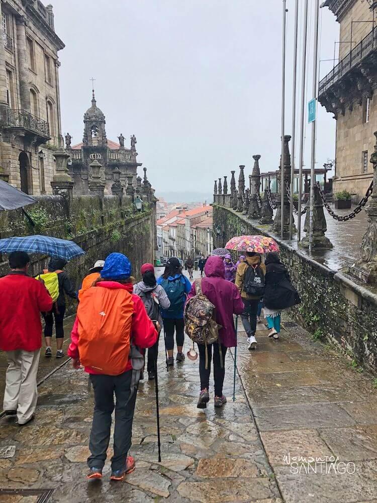 peregrinos con paraguas caminando