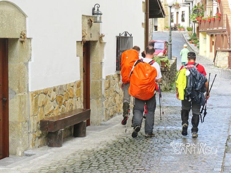 peregrinos con diferentes protecciones para la lluvia