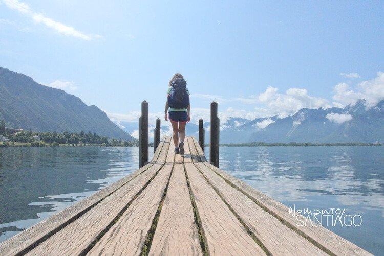 Mujer con mochila en embarcadero de un lago