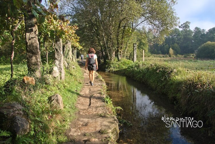 mujer haciendo el Camino de Santiago junto a un arroyo