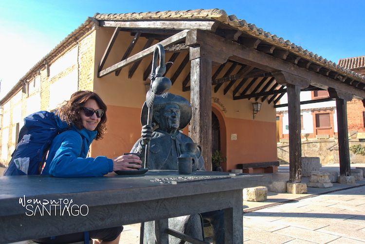 Peregrina sentada en una mesa con una estatua del Camino de Santiago